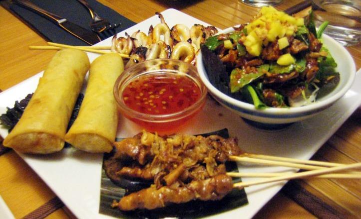 Surtido de entrantes: rollitos vegetarianos, brochetas de calamar, ensalada con pato y brochetas de pollo con salsa de cacahuetes